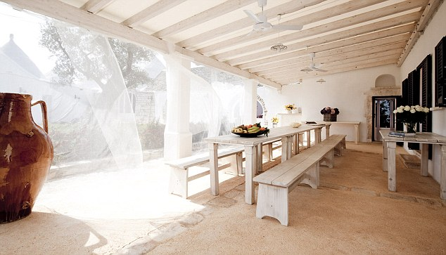 Light and breezy outdoor dining area with long table and pews