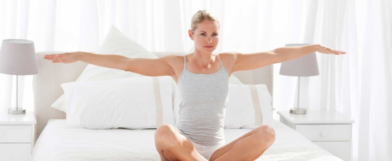Woman practising yoga on a white bed