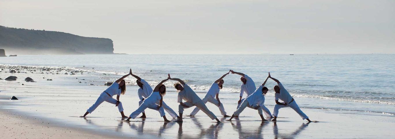 Group of visitors doing yoga on the beach at Paradis Plage