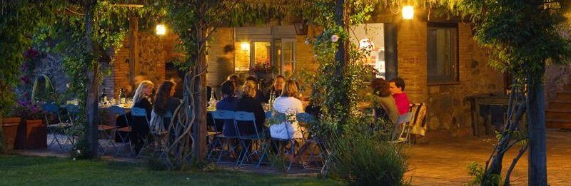 A group of singles sit outside eating dinner on a yoga retreat