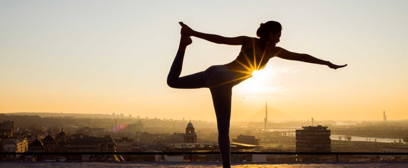 Woman practising yoga above a city skyline